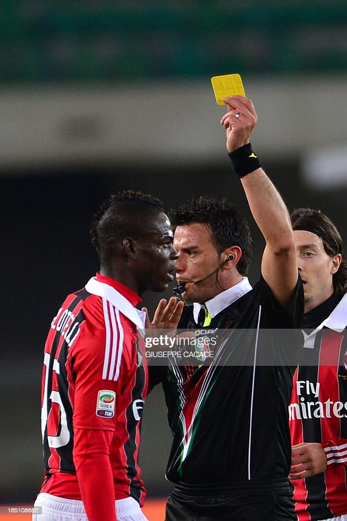 AC Milan's forward Mario Balotelli (L) receives a yellow card by referee Domenico Celi during the Seria A football match between Chievo and AC Milan at the 'Bentegodi Stadium' in Verona on March 30, 2013.