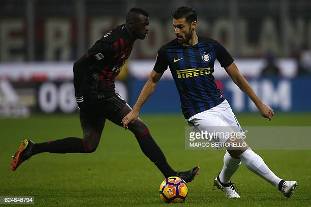 AC Milan's forward Mbaye Niang of France fights for the ball with Inter Milan's forward Antonio Candreva during the Italian Serie A football match AC...