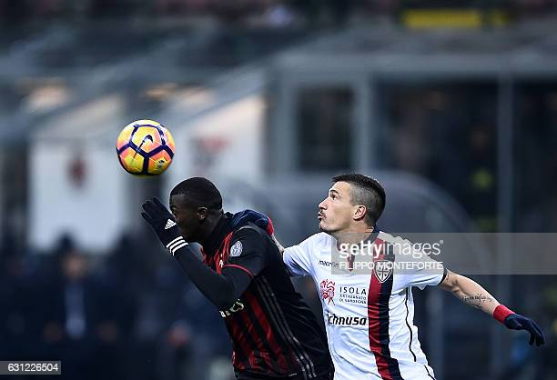 AC Milan's forward of France M'Baye Niang vies with Cagliari defender of Italy Fabio Pisacane during the Italian Serie A football match AC Milan vs...