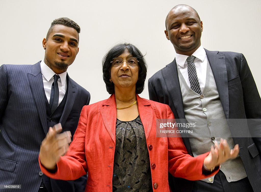AC Milan's Ghana international Kevin-Prince Boateng (L) and former France captain Patrick Vieira (R) pose with United Nations High Commissioner for Human Rights Navi Pillay (C) prior to the opening of a the panel discussion on racism and sport on March 21, 2013 at the United Nations Office in Geneva, Boateng, lauded by anti-racism campaigners since he walked off a football pitch during a club game in Italy to protest abuse by fans, joined Vieira and officials from FIFA, UEFA and the United Nations to discuss how to rid sport of the problem. AFP PHOTO / FABRICE COFFRINI