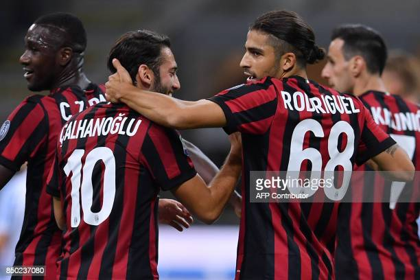 AC Milan's Italian defender Ricardo Rodriguez celebrates with AC Milan's Turkish forward Hakan Calhanoglu after scoring during the Italian Serie A...