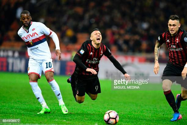 AC Milan's Italian forward Gianluca Lapadula is tackled by Genoa's French midfielder Olivier Ntcham during the Italian Serie A football match AC...