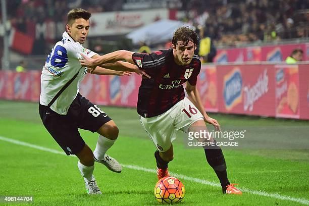 AC Milan's Italian midfielder Andrea Poli challenges Atalanta's Italian midfielder Alberto Grassi during the Serie A football match between AC Milan...