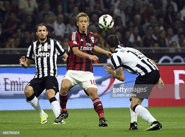 AC Milan's japanese forward Keisuke Honda fights for the ball with Juventus defender Leonardo Bonucci on September 20 2014 during a Serie A match...