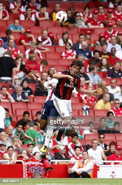 AC Milan's Massimo Oddo and Olympique Lyonnais' Michel Bastos battle for the ball