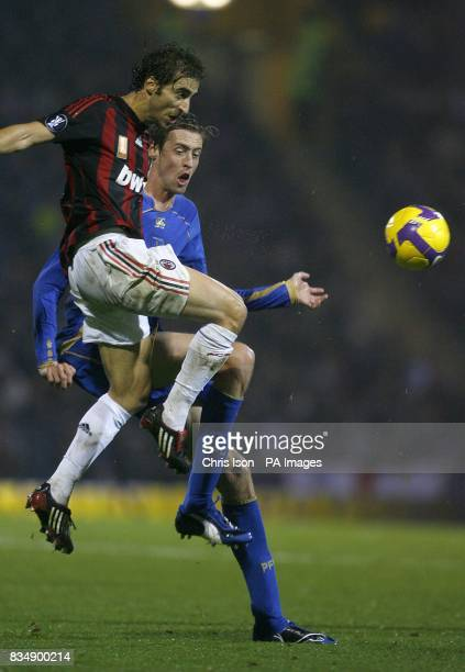 AC Milan's Mathieu Flamini and Portsmouth's Peter Crouch battle for the ball
