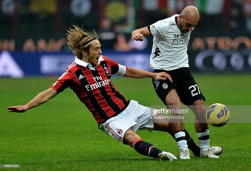 AC Milan's midfielder and captain Massimo Ambrosini L fight for the ball with Siena's striker Alessandro Rosina during the Italian Serie A football match between Ac Milan and Siena on January 6 , 2013 at San Siro stadium in Milan.