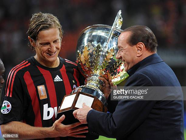 AC MIlan's midfielder and captain Massimo Ambrosini receives the cup from Italian Prime Minister Silvio Berlusconi during their 'XVIII Luigi...