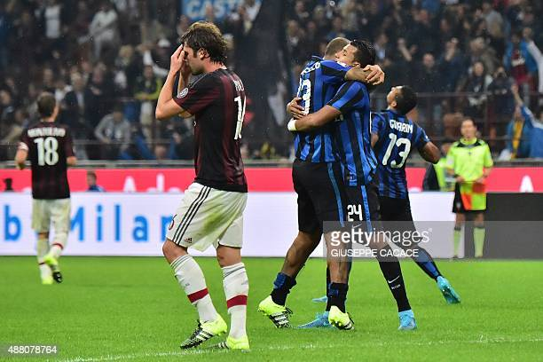 AC Milan's midfielder Andrea Poli reacts while Inter Milan's players celebrate at the end of the Italian Serie A football match between AC Milan and...