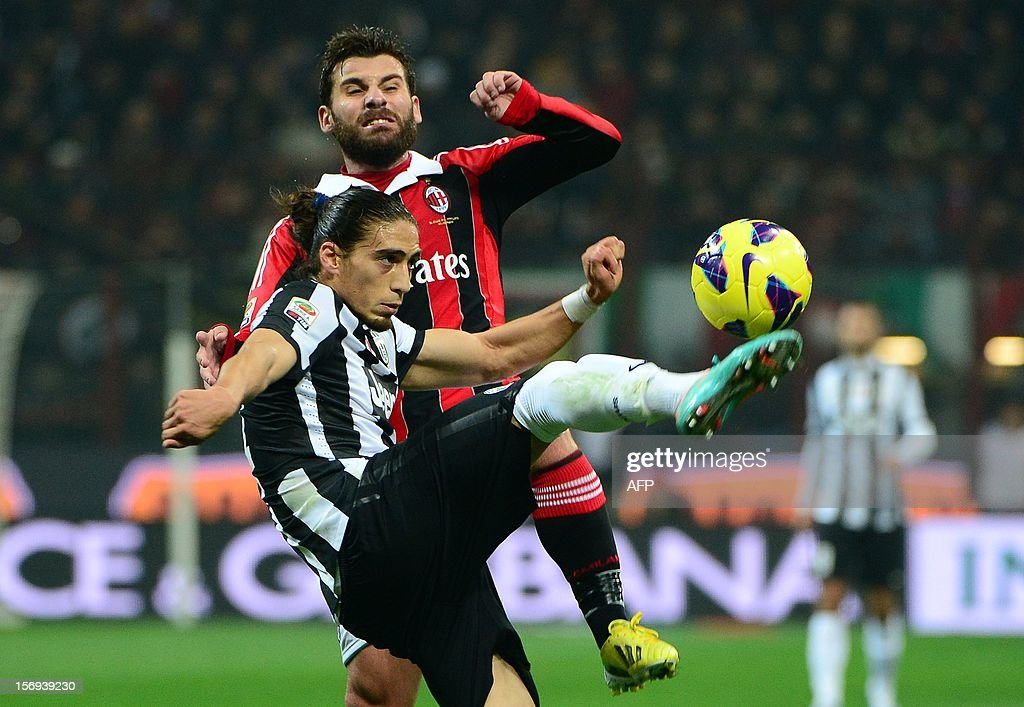 AC Milan's midfielder Antonio Nocerino (up) fights for the ball with Juventus' Uruguaian defender Martin Caceres during the Italian serie A football match between AC Milan and Juventus on November 25, 2012 at the San Siro stadium in Milan.