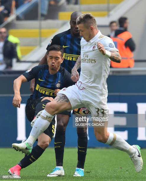 AC Milan's midfielder from Slovenia Juraj Kucka fights for the ball with Inter Milan's defender from Japan Yuto Nagatomo during the Italian Serie A...