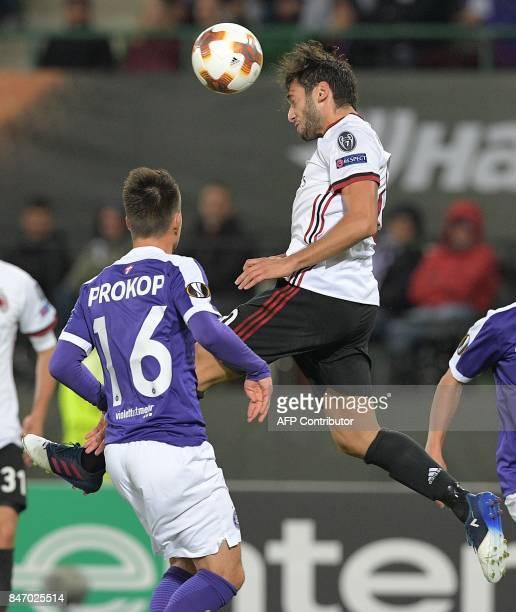 AC Milan's midfielder from Turkey Hakan Calhanoglu heads the ball during the UEFA Europa League group D football match FK Austria Wien v AC Milan in...