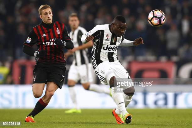 AC Milan's midfielder Gerard Deulofeu from France fights for the ball with Juventus' midfielder Kwadwo Asamoah from Ghana during the Italian Serie A...