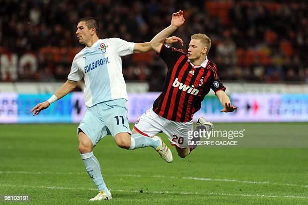 AC Milan's midfielder Ignazio Abate is airborne by Lazio's Serbian defender Aleksandar Kolarov during their Serie A football match AC Milan vs Lazio...