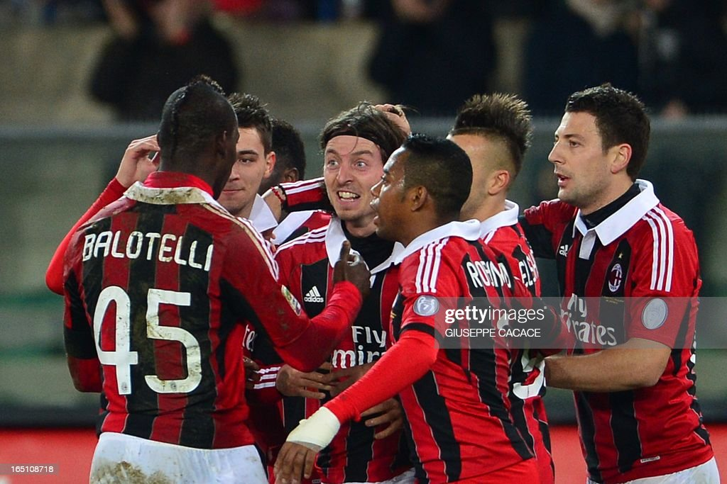 AC Milan's midfielder Riccardo Montolivo (C) celebrates with Mario Balotelli (L) and teammates after scoring during the Serie A football match between Chievo and AC Milan at the 'Bentegodi Stadium' in Verona on March 30, 2013. AFP PHOTO / GIUSEPPE CACACE