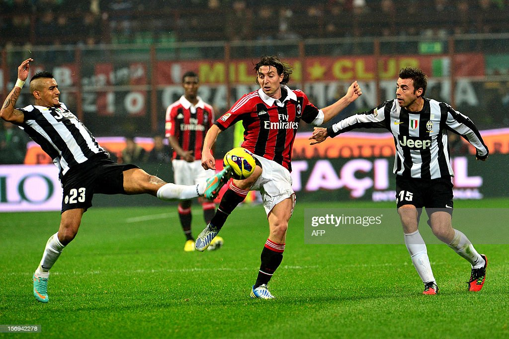 AC Milan's midfielder Riccardo Montolivo (C) fights for the ball with Juventus' midfielder of Chile Arturo Vidal (L) and Juventus' defender Andrea Barzagli during the Italian serie A football match between AC Milan and Juventus on November 25, 2012 at the San Siro stadium in Milan.
