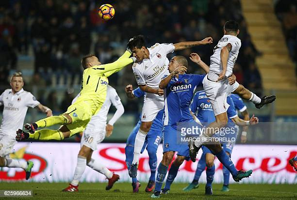 AC Milan's Paraguayan defender Gustavo Gomez jumps for the ball with Empoli's Polish goalkeeper Lukasz Skorupski during the Italian Serie A football...