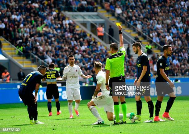 AC Milan's Slovenian midfielder Juraj Kucka receives a yellow card during the Italian Serie A football match Inter Milan vs AC Milan at the San Siro...