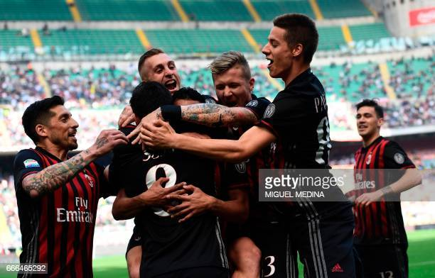 AC Milan's Spanish forward Fernandez Suso celebrates with teammates after scoring during the Italian Serie A football match AC Milan vs Palermo at...