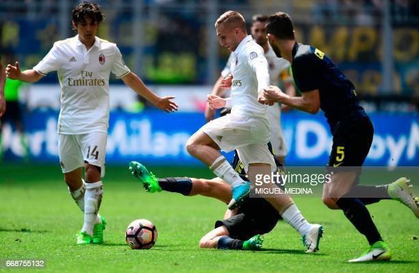 AC Milan's Spanish forward Gerard Deulofeu vies with Inter Milan's Italian midfielder Antonio Candreva and Inter Milan's Italian midfielder Roberto...