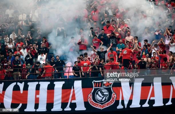 AC Milan's supporters celebrate a goal during the Italian Serie A football match Inter Milan vs AC Milan at 'San Siro' Stadium in Milan on April 15...