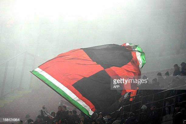 AC Milan's supporters wave a flag at the end of the Serie A football match between AC Milan and Pescara at San Siro Stadium in Milan on December 16...