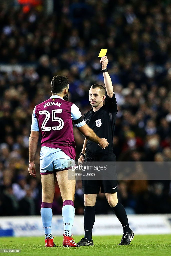 Mile Jedinak of Aston Villa is issued a yellow card for an illegal tackle against Hadi Sacko of Leeds United during the Sky Bet Championship match between Leeds United v Aston Villa at Elland Road on December 3, 2016 in Leeds, England.