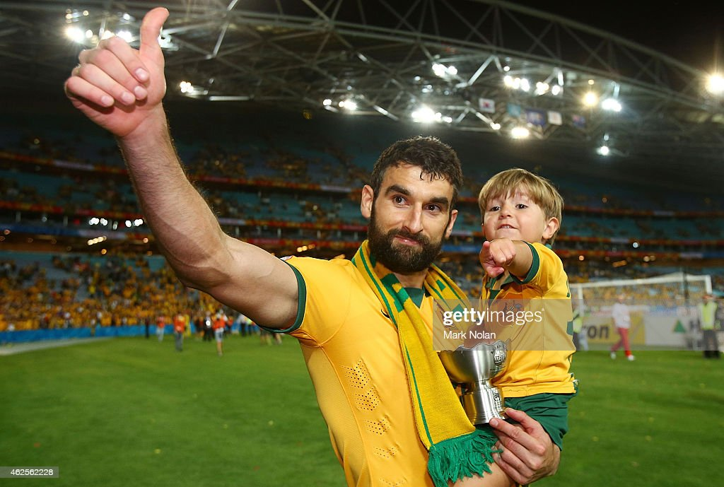 Mile Jedinak of Australia carries his son on the victory lap after the 2015 Asian Cup final match between Korea Republic and the Australian Socceroos at ANZ Stadium on January 31, 2015 in Sydney, Australia.