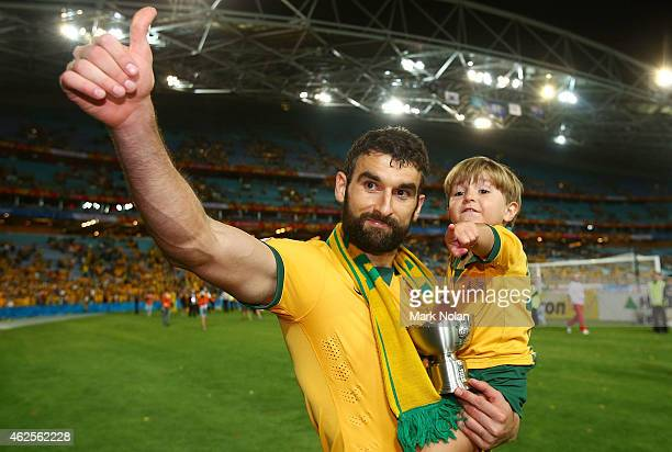 Mile Jedinak of Australia carries his son on the victory lap after the 2015 Asian Cup final match between Korea Republic and the Australian Socceroos...