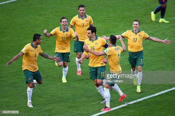 Mile Jedinak of Australia celebrates scoring his team's second goal with teammates during the 2014 FIFA World Cup Brazil Group B match between...