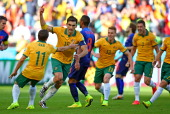 Mile Jedinak of Australia celebrates with teammates after scoring the team's second goal from the penalty spot during the 2014 FIFA World Cup Brazil...