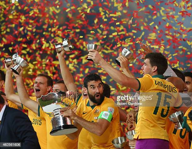 Mile Jedinak of Australia celebrates with the winners trophy after Australia defeated Korea republic at the 2015 Asian Cup final match between Korea...