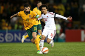 Mile Jedinak of Australia contests the ball with Omar Abdulrahman of The United Arab Emirates during the Asian Cup Semi Final match between the...