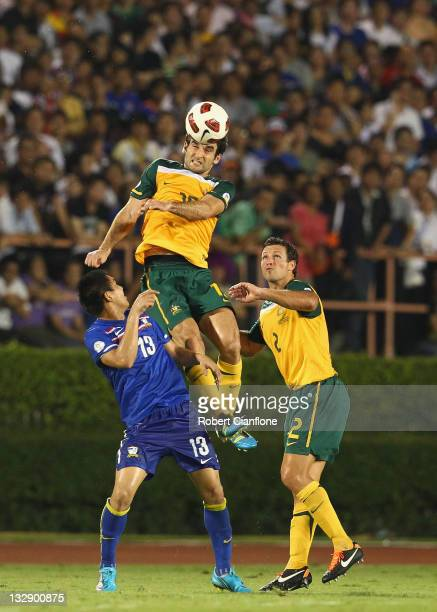 Mile Jedinak of Australia heads the ball over the top of Kirati Keawsombut of Thailand during the 2014 FIFA World Cup Asian Qualifier match between...