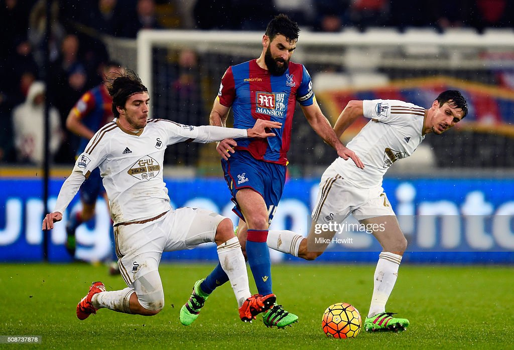 Mile Jedinak (C) of Crystal Palace competes for the ball against Alberto Paloschi (L) and Jack Cork (R) of Swansea City during the Barclays Premier League match between Swansea City and Crystal Palace at the Liberty Stadium on February 6, 2016 in Swansea, Wales.