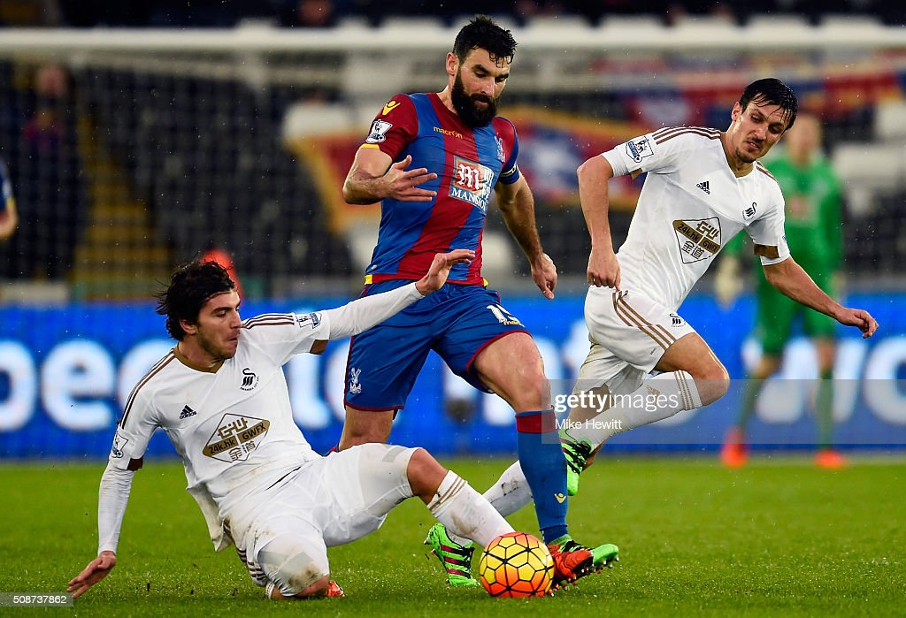 Mile Jedinak of Crystal Palace is tackled by Alberto Paloschi of Swansea City during the Barclays Premier League match between Swansea City and Crystal Palace at the Liberty Stadium on February 6, 2016 in Swansea, Wales.