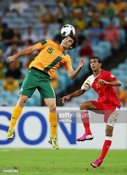 Mile Jedinak of the Socceroos heads the ball in front of Amad Al Hosni of Oman during the FIFA 2014 World Cup Qualifier match between the Australian...