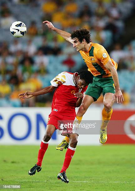 Mile Jedinak of the Socceroos jumps above Raed Saleh of Oman during the FIFA 2014 World Cup Qualifier match between the Australian Socceroos and Oman...