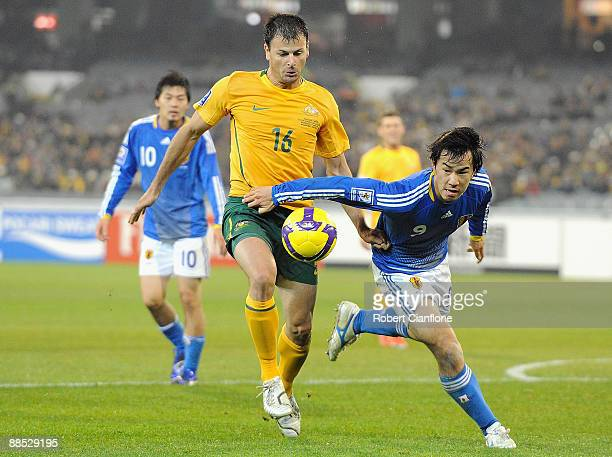 Mile Sterjovski of Australia challenges Shinji Okazaki of Japan during the 2010 FIFA World Cup Asian qualifying match between the Australian...