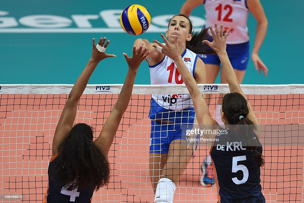 Milena Rasic of Serbia spikes as Robin De Kruijf (R) and Celeste Plak (L) of Netherlands block during the FIVB Women's World Championship pool F match between Serbia and Netherlands on October 1, 2014 in Verona, .