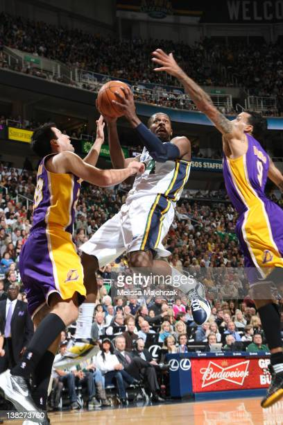 J Miles of the Utah Jazz takes a shot over Jason Kapono and Matt Barnes of the Los Angeles Lakers at Energy Solutions Arena on February 04 2012 in...