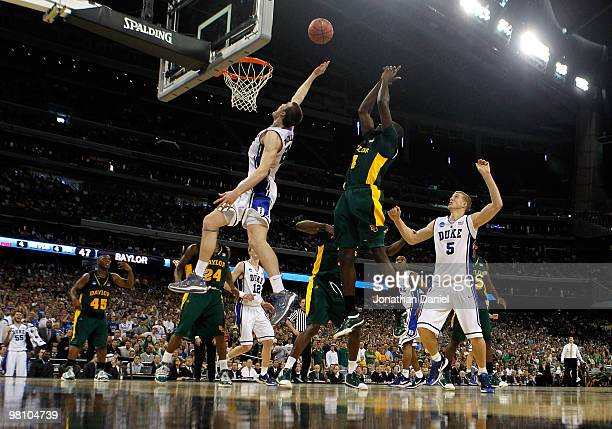 Miles Plumlee of the Duke Dlue Devils leaps for a rebound in front of Quincy Acy of the Baylor Bears during the south regional final of the 2010 NCAA...