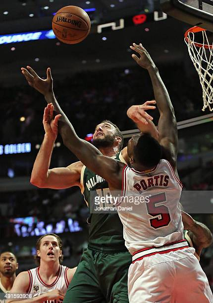 Miles Plumlee of the Milwaukee Bucks battles for a rebound with Bobby Portis of the Chicago Bulls during a preseason game at the United Center on...