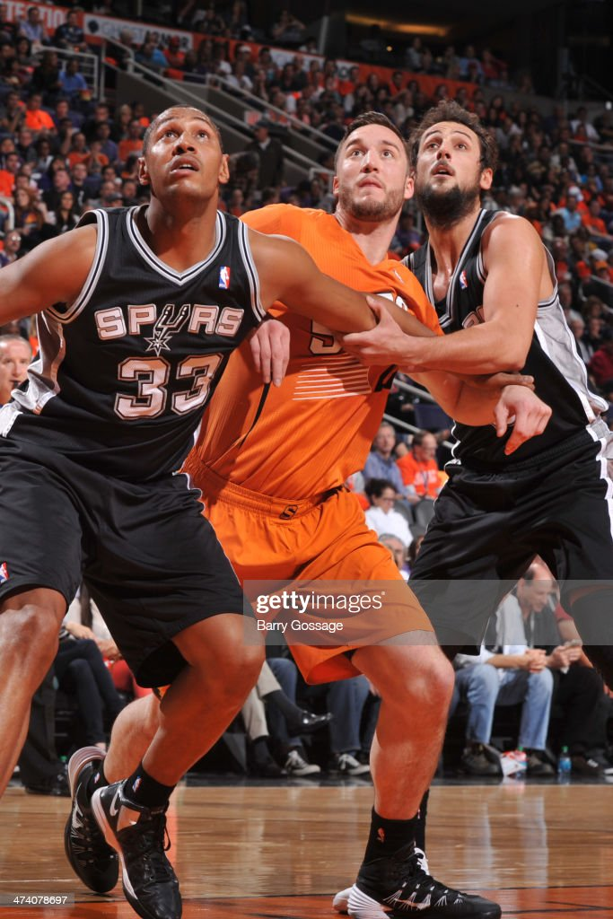 Miles Plumlee #22 of the Phoenix Suns battles for position against Boris Diaw #33 and Marco Belinelli #3 of the San Antonio Spurs on February 21, 2014 at U.S. Airways Center in Phoenix, Arizona.