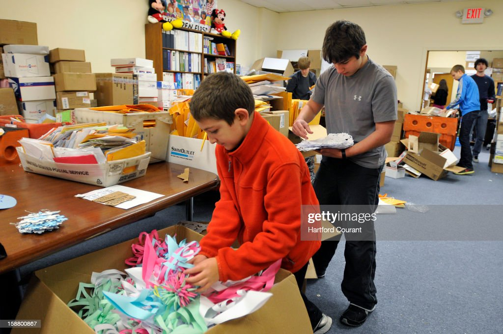 Miles Savatz, 11, and his brother Sam, 16, sort through some of the thousands of parcels sent to the Connecticut Parent Teacher Student Association, which is collecting snowflakes to create a Winter Wonderland for the kids of Sandy Hook Elementary School, in Hamden, Connecticut, Friday, December 28, 2012.