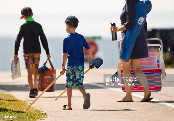Miles Thebarge of Brunswick carries his shovel and rake while walking to Higgins Beach with his Brother Declan and mom Shiloh Thebarge on Monday...