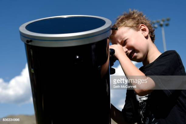 Miles Thiry peers through a telescope at the sun during a solar eclipse viewing party at Colorado School of Mines on August 21 in Golden Colorado The...