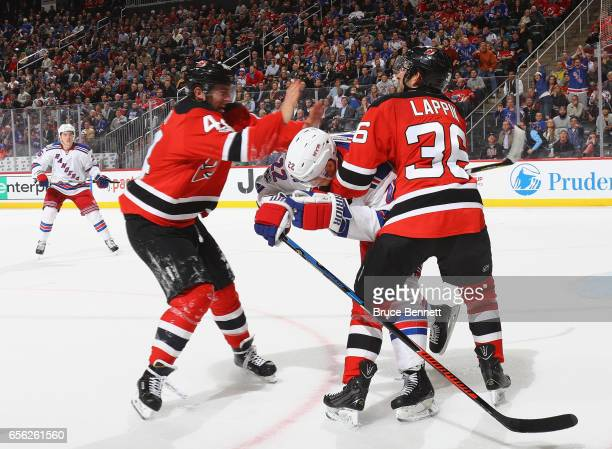 Miles Wood and Nick Lappin of the New Jersey Devils go after Nick Holden of the New York Rangers after a second period hit at the Prudential Center...