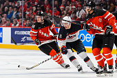 Miles Wood of Team United States skates in between Jake Virtanen of Team Canada and teammate Madison Bowey in a preliminary round game at the 2015...