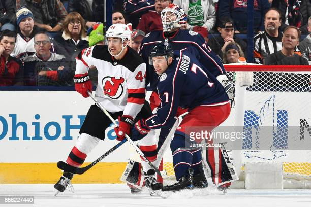 Miles Wood of the New Jersey Devils and Jack Johnson of the Columbus Blue Jackets battle for position on December 5 2017 at Nationwide Arena in...